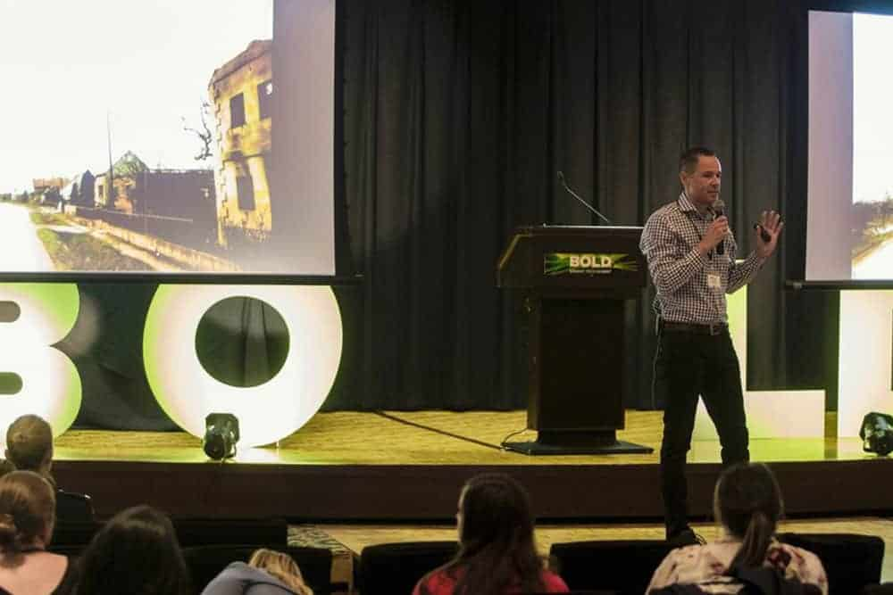 Photograph of Tom Morin on stage presenting at the Bold Summit, June 2018. Behind him are photographs of burned villages common to the 1993 landscape of the former-Yugoslavia.