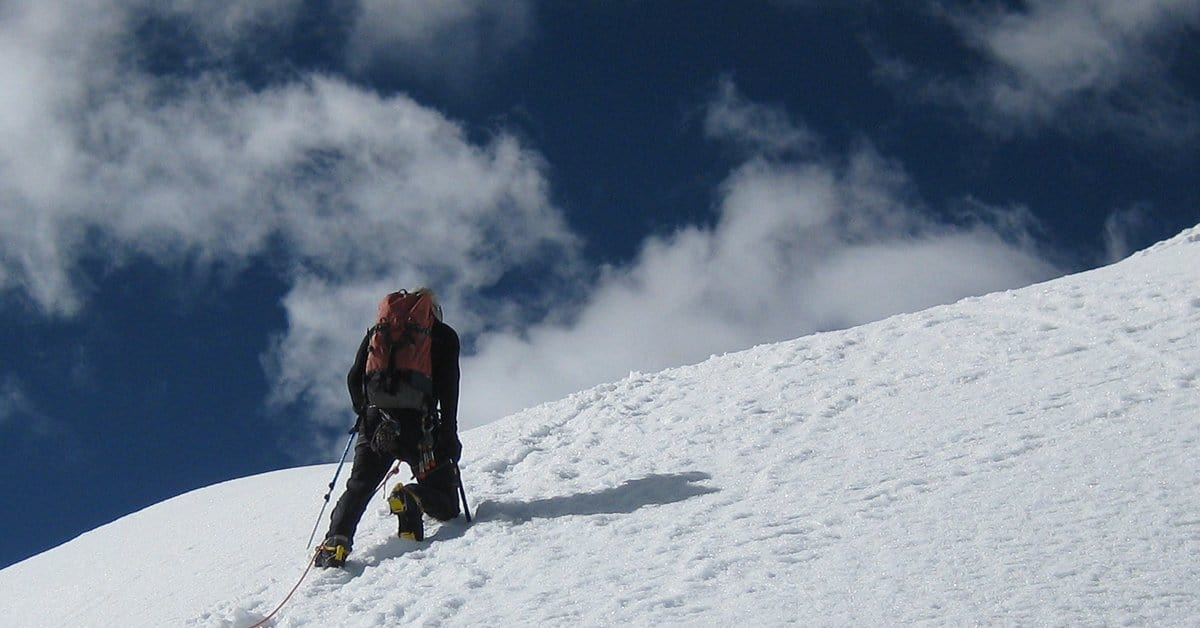 Photograph of Tom Morin climbing Mout Inshinca in Peru. He is climbing up a snow slope just below the summit. The photo was taken on the day he started his journey toward meaningful work.