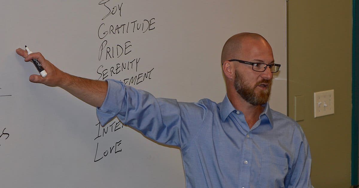 Paul Krismer standing in front of a white board and speaking to workshop attendees. On the white board, he has written the words joy, gratitude, pride, serenity and love.