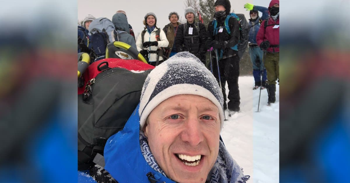 Photo of Mark Little with a group of Adventurer Scouts behind him. They are getting ready for a snowshoeing trip.