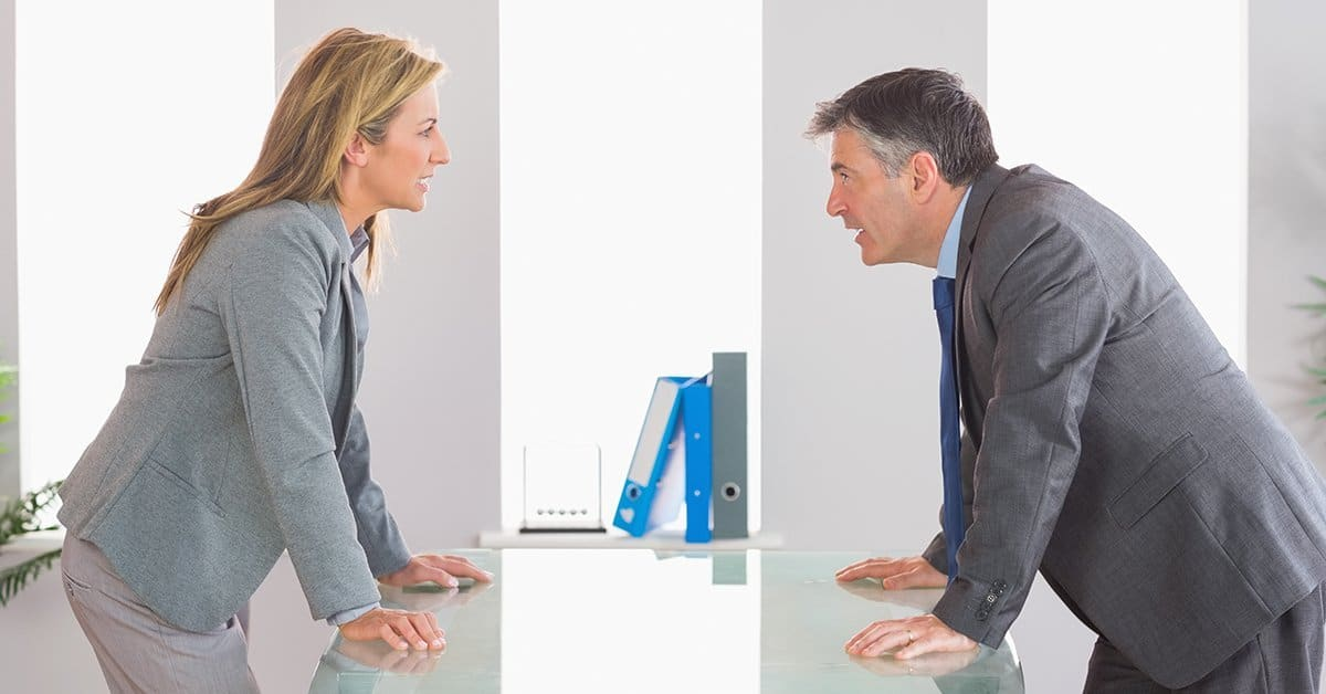 Woman and man standing on either side of a large desk facing each other. They appear angry.