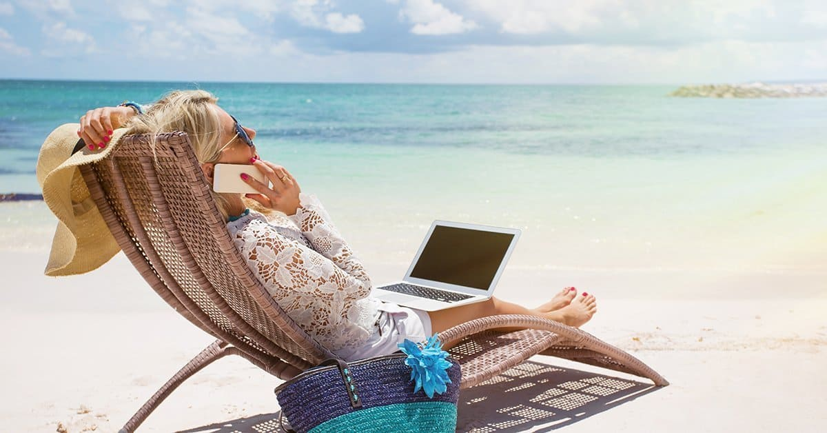Photograph of a business woman relaxing in a beach chair, talking on her phone.